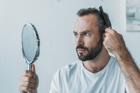 bearded middle aged man combing hair and looking at mirror, hair loss concept Stockfoto