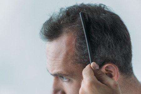 close-up view of mid adult man combing hair with comb isolated on grey, hair loss concept