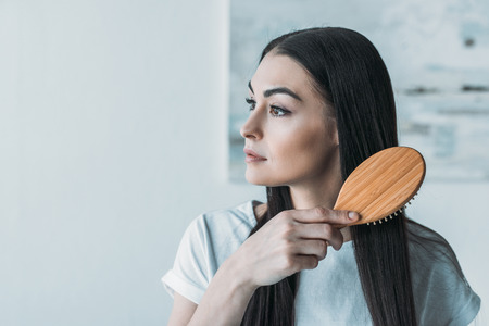 young brunette woman combing hair with hairbrush and looking away