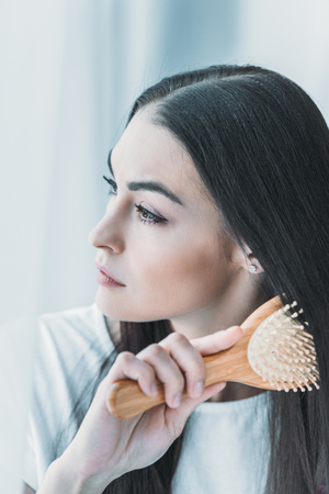 young pensive brunette woman combing hair with hairbrush and looking away Foto de archivo - 110961524