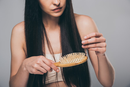 cropped shot of young brunette woman combing hair with hairbrush isolated on grey, hair loss concept Stock fotó