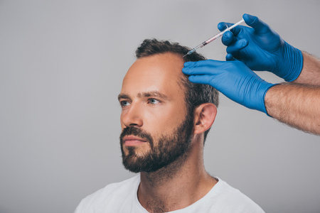 cropped shot of doctor with syringe giving injection to man with alopecia looking away isolated on grey