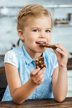 cute happy kid eating delicious chocolate with hazelnuts and smiling at camera