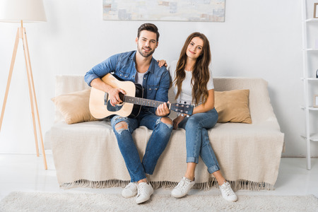 happy young couple sitting on couch with acoustic guitar and looking at camera at home Banco de Imagens