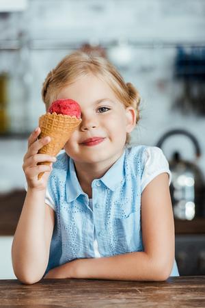 cute happy kid holding delicious sweet ice cream cone and smiling at camera Foto de archivo - 112354838