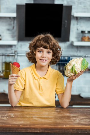 cute happy child holding sweet ice cream and healthy cauliflower, smiling at camera