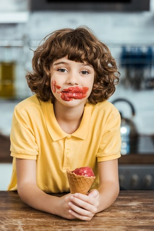 adorable boy with ice cream on face holding delicious ice cream cone and looking at camera Stockfoto