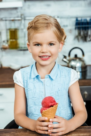 cute happy kid holding delicious sweet ice cream cone and smiling at camera