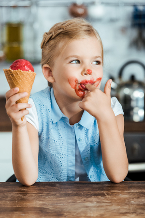 adorable little child eating sweet ice cream and licking finger Stock Photo