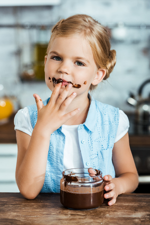 cute little child eating delicious chocolate spread and looking at camera 스톡 콘텐츠