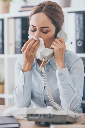 close-up portrait of diseased businesswoman with runny nose talking by wired phone at office 版權商用圖片
