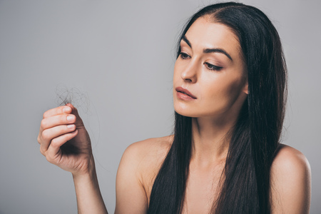 young brunette woman holding fallen hair isolated on grey, hair loss concept