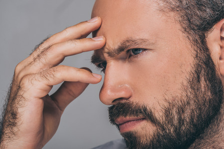close-up view of sad bearded man with hand on forehead looking away isolated on grey