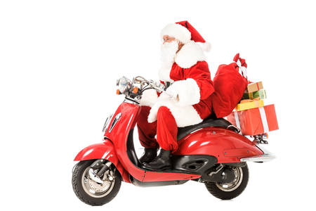 side view of santa claus riding vintage red scooter with sacks and gift boxes isolated on white
