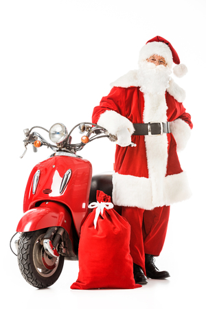 santa claus with vintage red scooter and sack looking at camera isolated on white