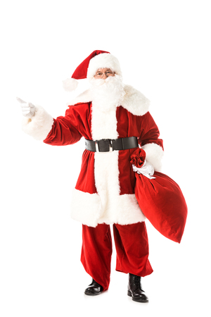 santa claus holding sack and pointing away while looking at camera isolated on white