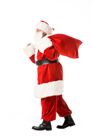 side view of santa claus walking with sack isolated on white
