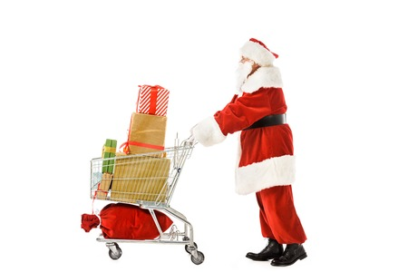 side view of santa claus walking with shopping cart full of christmas gift boxes isolated on white Banco de Imagens