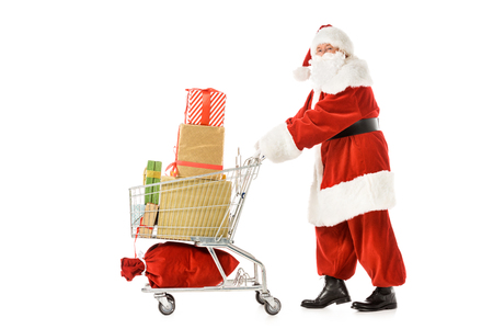 side view of santa claus walking with shopping cart full of gift boxes isolated on white Stock Photo
