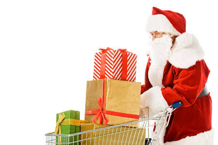 santa claus with shopping cart full of gift boxes isolated on white Stock Photo