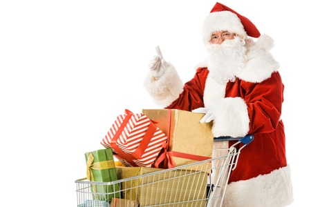 santa claus with shopping cart full of gift boxes pointing up isolated on white Stock Photo
