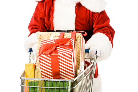 cropped shot of santa claus driving shopping cart full of gift boxes isolated on white