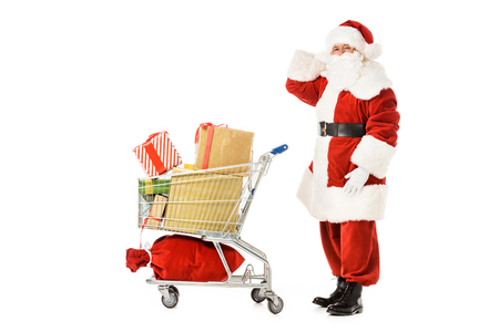 side view of bewildered santa claus with shopping cart looking at camera isolated on white