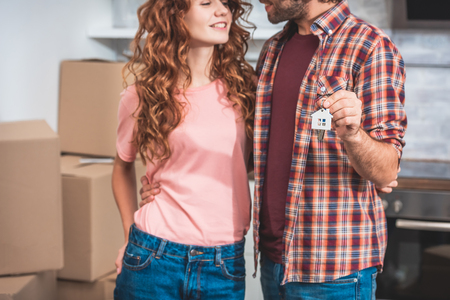 cropped image of smiling couple hugging and holding house trinket with keys at new home