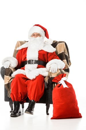 santa claus sitting in armchair and looking at camera isolated on white