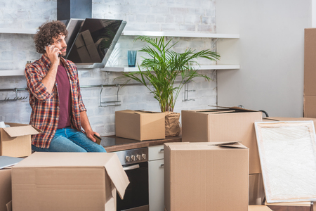 young man talking by smartphone and looking away while sitting between cardboard boxes in new apartment