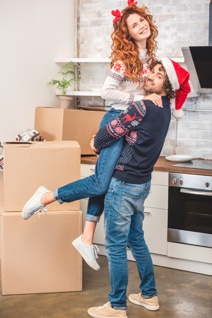happy young couple hugging and smiling at camera while relocating at christmastime Stock Photo