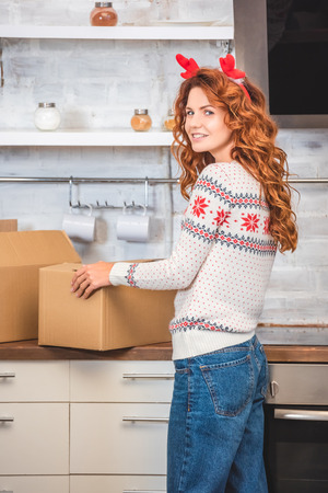 beautiful young woman in antlers headband holding cardboard box and smiling at camera while relocating in new apartment Stock Photo