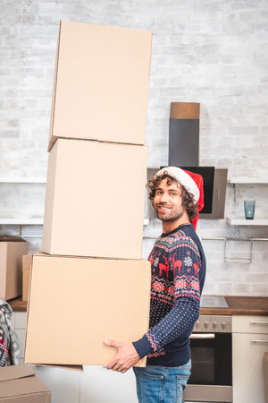 handsome happy man in santa hat holding cardboard boxes and smiling at camera Stock Photo