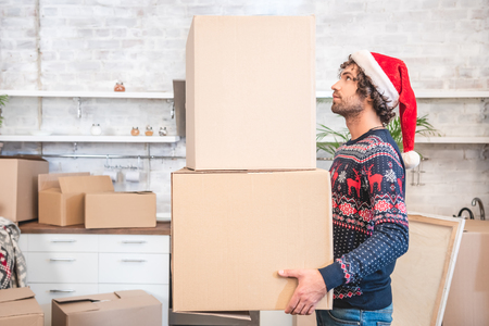side view of young man in santa hat holding cardboard boxes during relocation Stock Photo