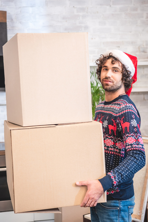 handsome young man in santa hat holding cardboard boxes and smiling at camera