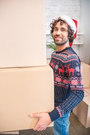 happy young man in santa hat holding cardboard boxes and smiling at camera Stock Photo