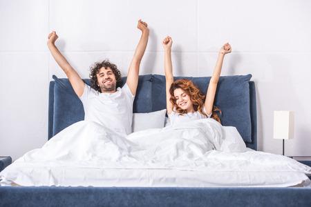 Feliz pareja joven estirando los brazos y despertando juntos en el dormitorio