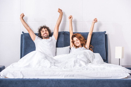 happy young couple stretching arms and waking up together in bedroom Фото со стока - 111744455