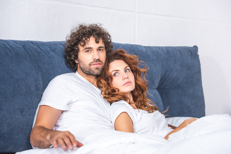 beautiful young couple lying together on bed, man looking at camera Standard-Bild - 111171242