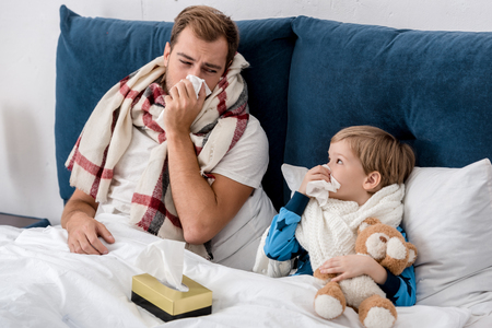 father and son blowing noses with paper napkins while lying in bed and looking at each other Stockfoto - 111105302