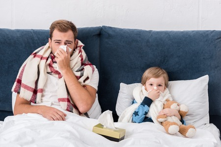 sick father and son blowing noses with paper napkins while lying in bed and looking at camera