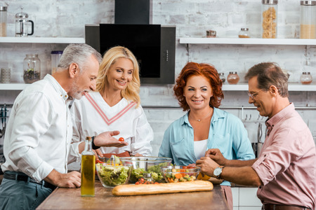 mature old friends preparing healthy salad for dinner at home Stok Fotoğraf
