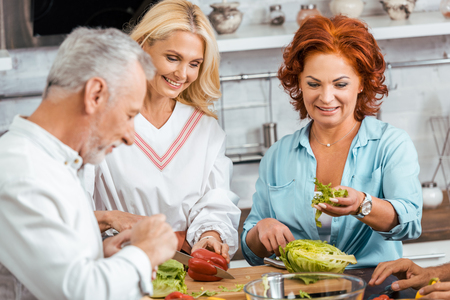 smiling mature friends preparing healthy detox salad for dinner at home Banco de Imagens