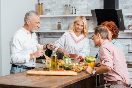 mature men and women preparing salad for dinner at home Imagens