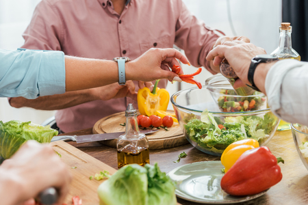 cropped image of mature friends preparing salad for dinner at home and putting ingredients in bowl Stok Fotoğraf