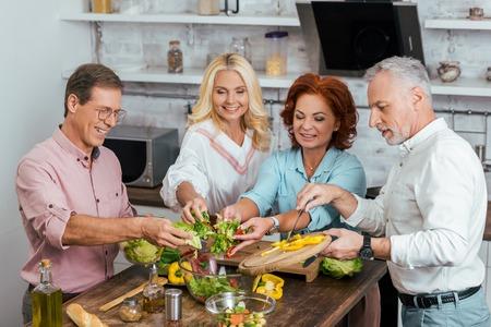 happy old friends preparing salad for dinner together at home and putting vegetables in bowl Banco de Imagens