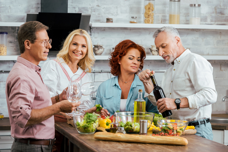 smiling mature friends celebrating meeting with salad and wine in kitchen