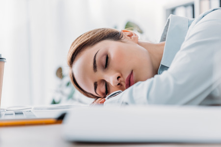 close-up shot of overworked adult businesswoman sleeping at workplace