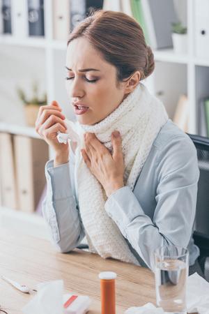 Erwachsene kranke Geschäftsfrau mit Husten, die am Arbeitsplatz im Schal sitzt