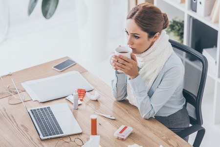 high angle view of sick businesswoman in scarf sitting at workplace and drinking tea